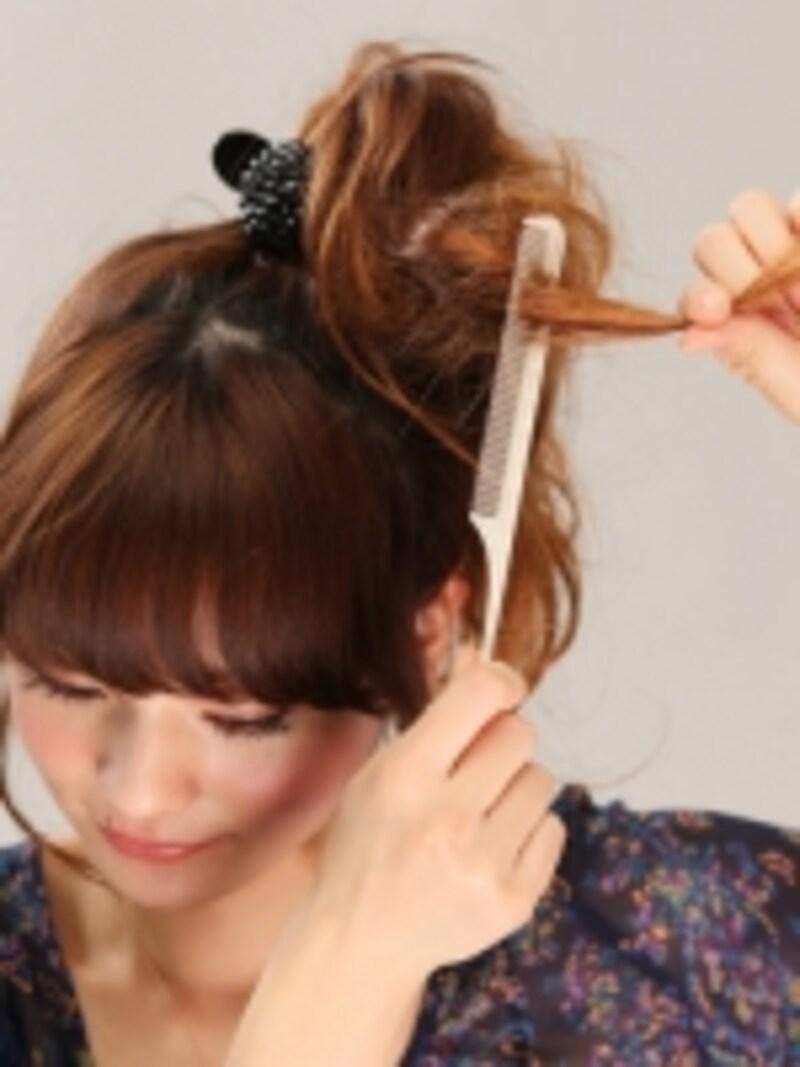 3ボリュームを出すためにポニーテールの髪の中間にしっかりと逆毛を立てる。