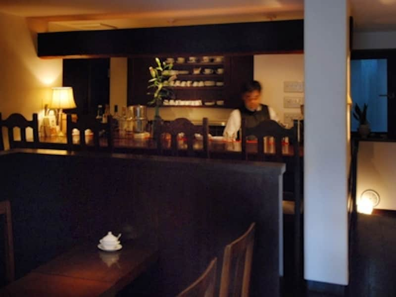 漆喰の壁、深い焦げ茶色の家具に囲まれた小空間。