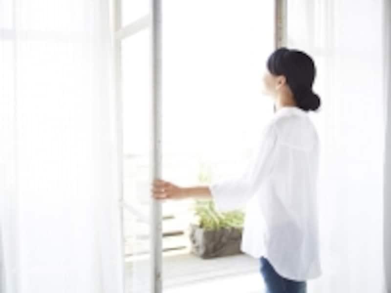 窓を開ける女