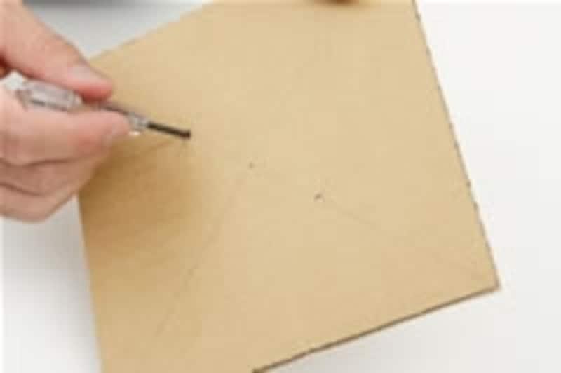 2.うすく鉛筆で対角線を描いて、中心を定めます。対角線を3等分するくらいの場所に2カ所小さな穴をあけます。穴が大きすぎると回りにくくなるので注意しましょう。