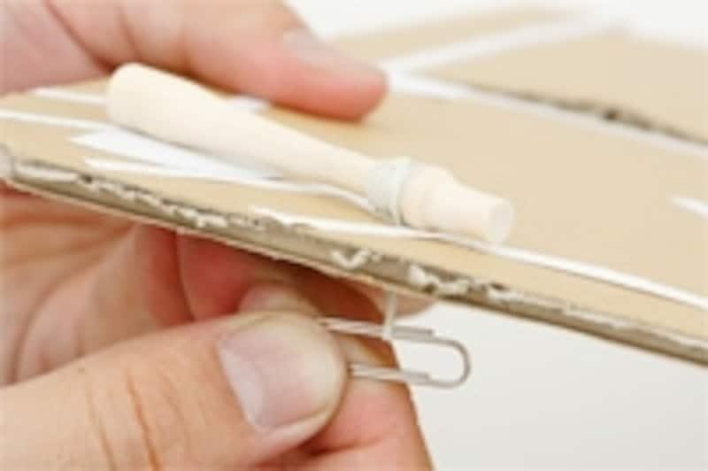 4.中敷の穴に通したゴムの先を、裏でゼムクリップにつなげば中敷きにバットが固定されます。バットがスムーズに動くかどうか確認しましょう。バットの素材はわりばしでも短くなった鉛筆でもなんでもかまいません。中敷きを枠箱にはめ込み、両面テープで発射台を取り付ければ完成です!