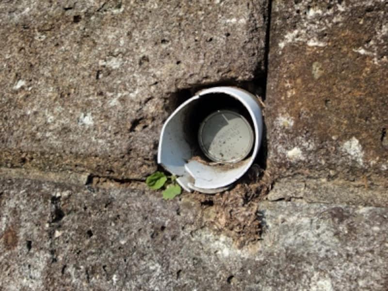 空き缶が詰め込まれた擁壁の水抜き穴