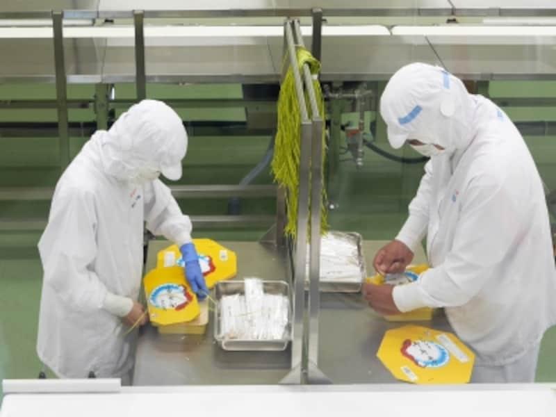 シウマイ弁当の紐は横浜の工場でつくられた証。人の手と合わせて「ひもかけ機」も導入されます(2017年7月12日撮影)