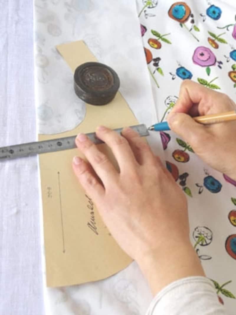 型紙は文鎮などでおさえ、定規を使いながらポイント、ポイントに印をつけていくと布地がズレにくい