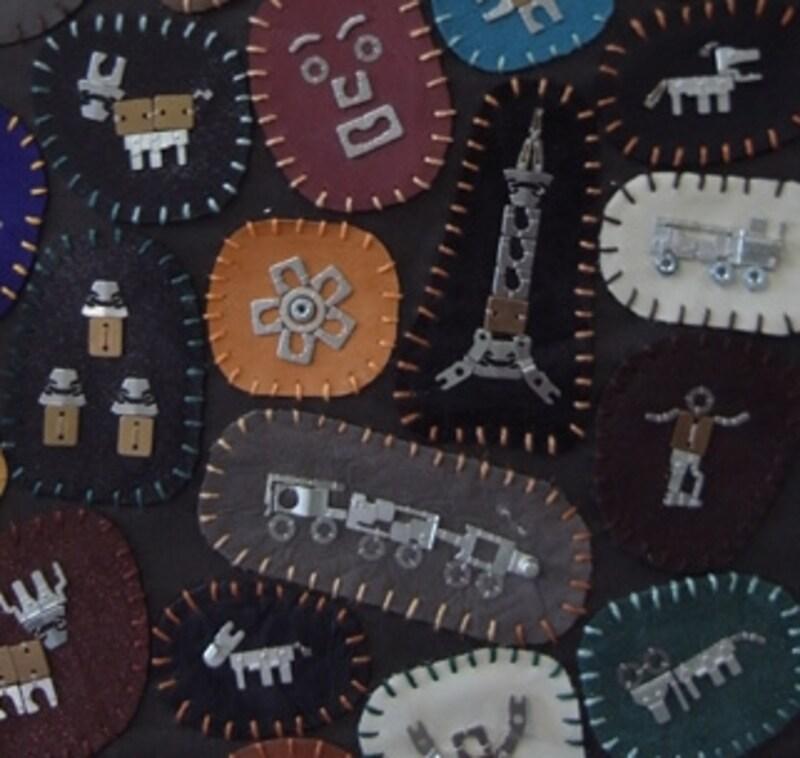 大須賀さんが最初に持ってきたというタペストリーの拡大(全体は上の写真)。金属部品の形に合わせた人や動物の表現に注目。ちゃんとスカイツリーもある!