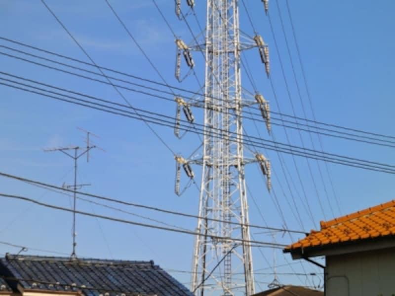 住宅脇に立つ鉄塔と送電線