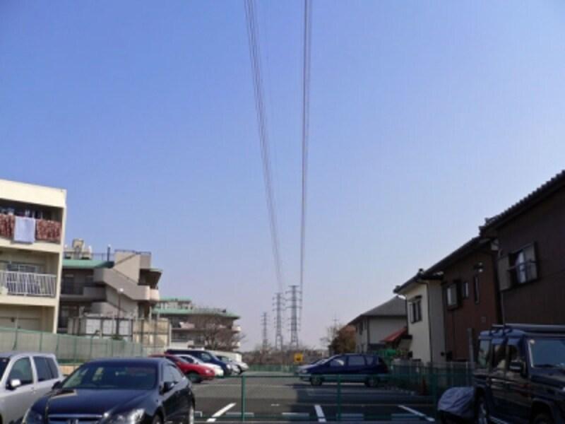 駐車場上空の鉄塔と送電線