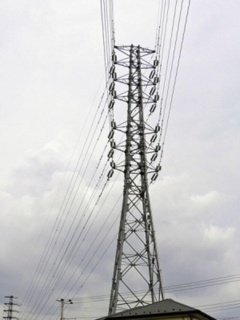 住宅の上にそびえる鉄塔と送電線