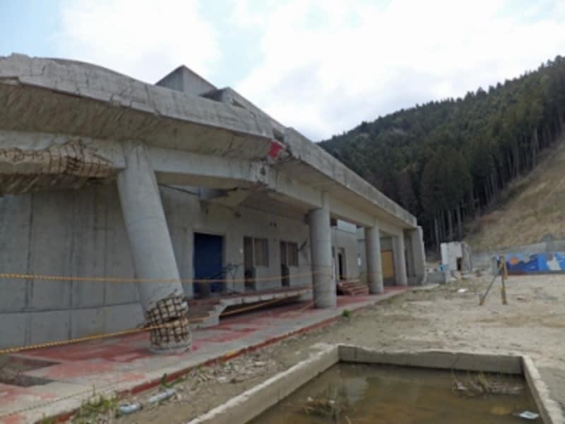 校舎とプール、体育館(と思われる)建物をつなぐ鉄筋コンクリートでできた渡り廊下の柱は根元から折れていた。
