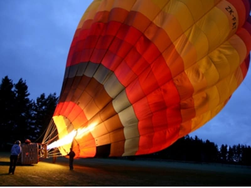 温かい空気がバルーン内に送り込まれてゆっくりと浮かび上がる熱気球