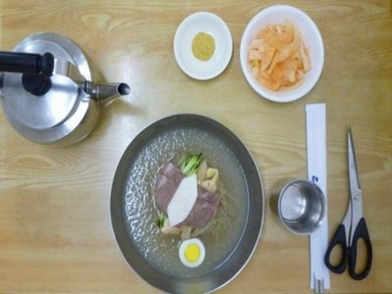冷麺を注文すると、ユクス(牛肉の煮込みスープ)が入ったヤカンと、麺を切るハサミがセットで出されます。ヤカンの代わりに、ユクスが入ったコップのこともあり