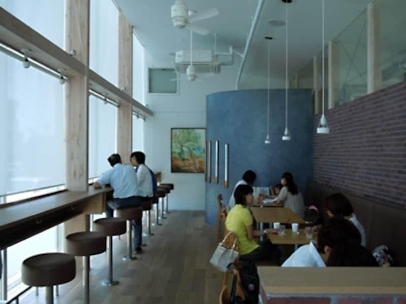 天井が高く、窓が大きく、開放感のある明るいカフェスペース