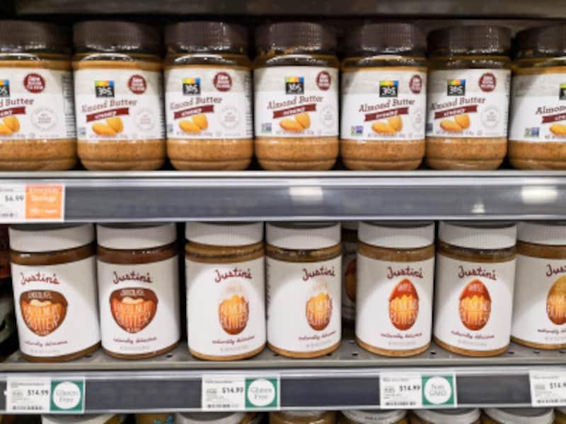 「365」の砂糖未使用ピーナッツバター(上段)。人気ブランド「ジャスティンズ」(下段)の約半額で購入できる