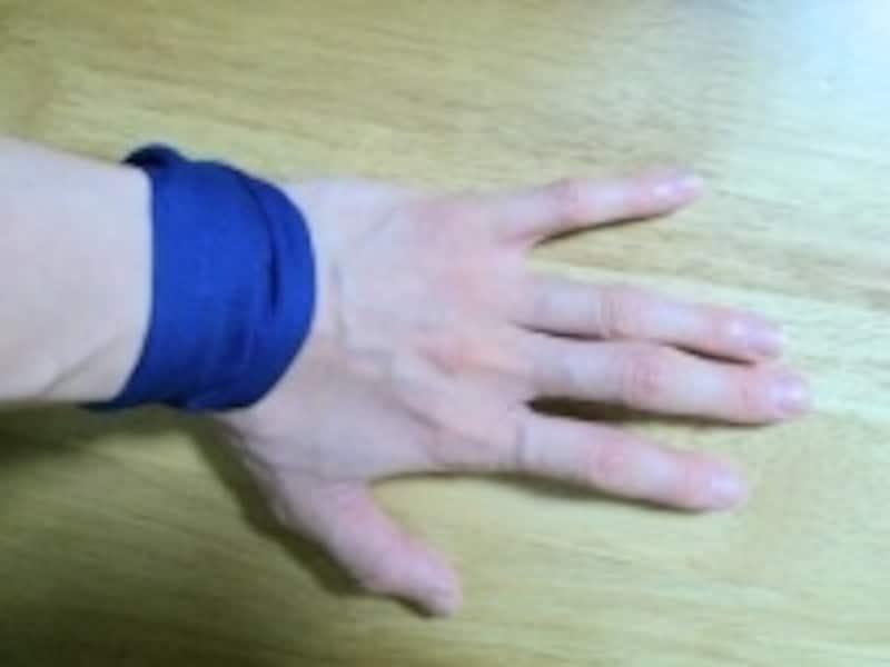 手首に布を強めに巻いて痛みが軽減するかチェックします
