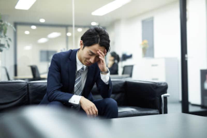 社内で落ち込んだ表情をするビジネスマン