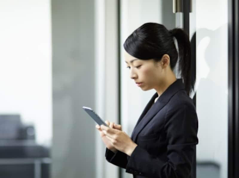 携帯を見る女性社員