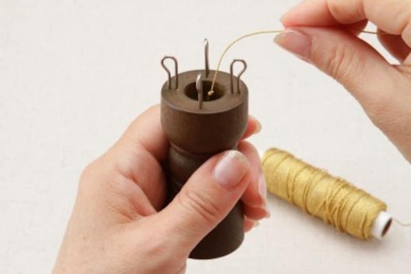 編み器の中央の穴に糸を通す