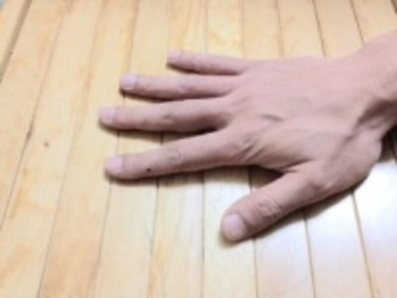 机に軽く手を載せたとき、緊張が強いとかなり指が曲がった状態に