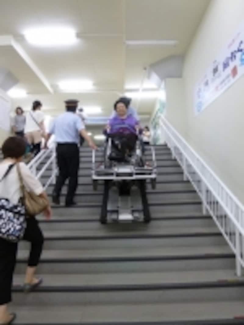 専用の装置を使って駅の階段を車いすで昇っているシーン