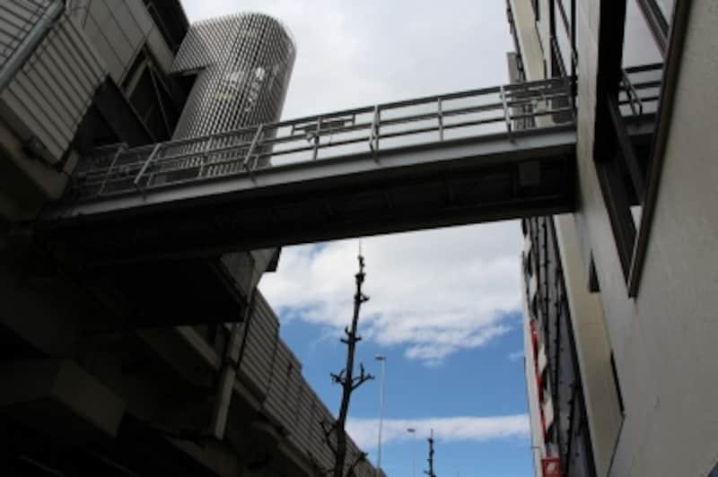シーンインテリジェントオートundefinedF9.01/200秒ISO100EF-S18-135mmf/3.5-5.6ISSTM20mm(32mm相当)「首都高速1号線」undefined首都高速1号線入谷料金所と隣のビルを結ぶ橋を見上げる。青い空と白い雲に露出を合わせる