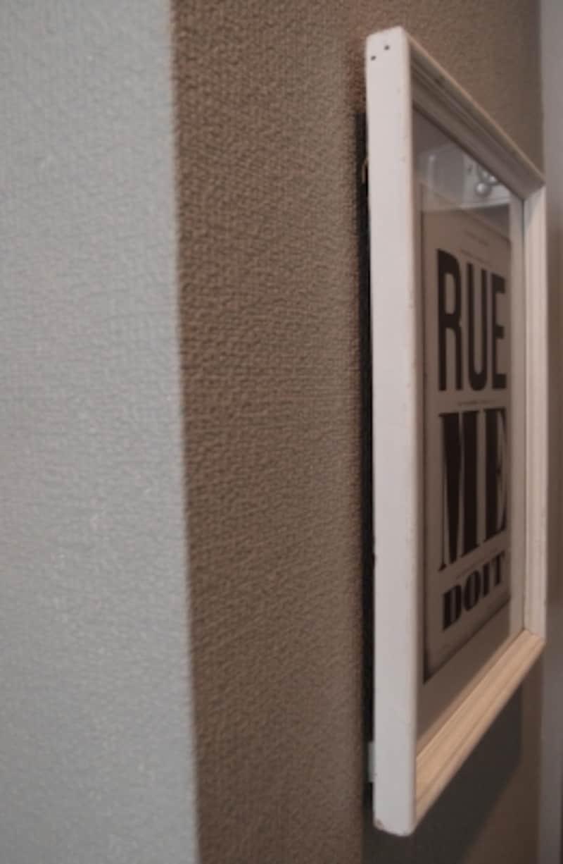 額を壁に掛ける。