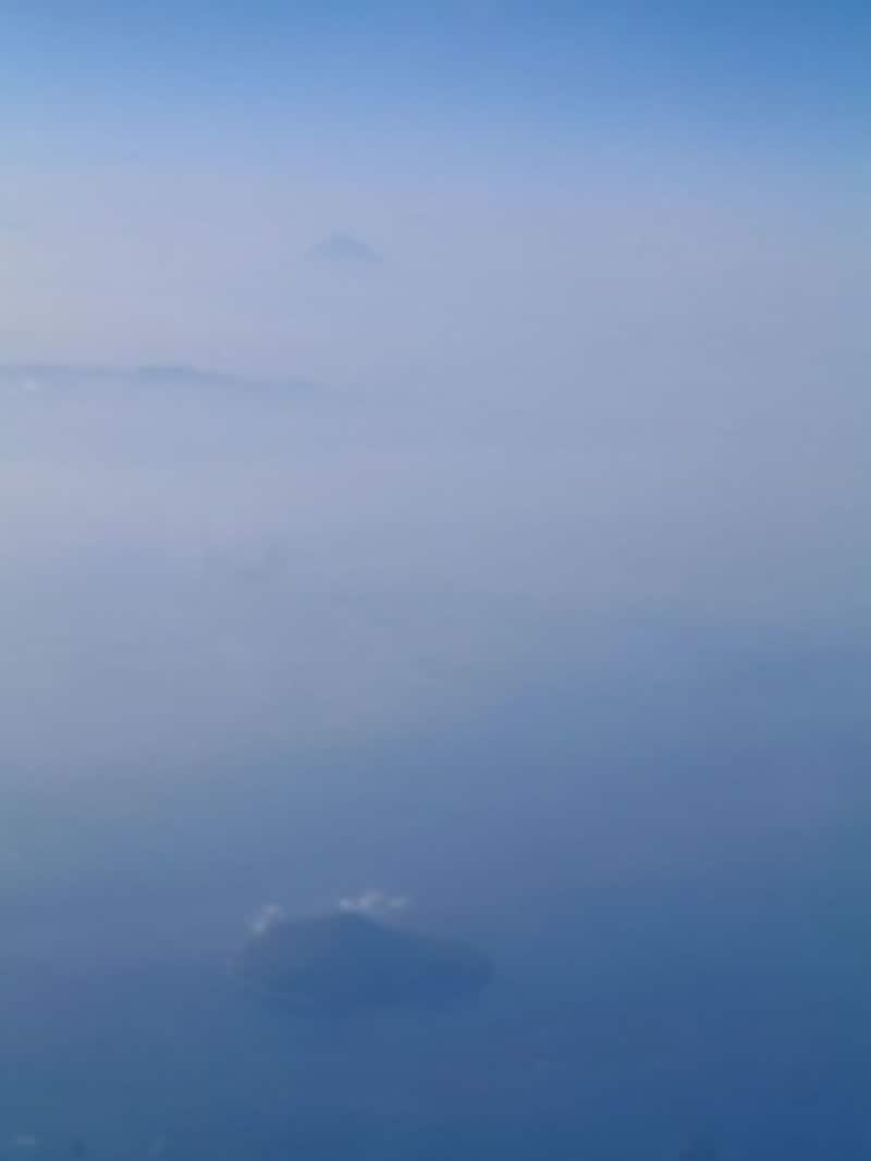 那覇発羽田行き飛行機から眺める富士山。利島の向こう、霞の中に富士山が見えます