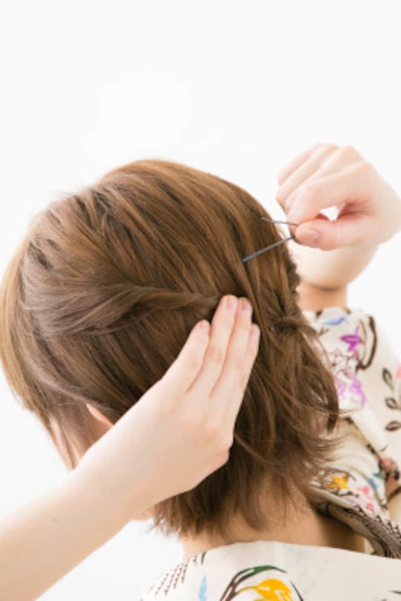 ねじった毛束をアメピンで固定する