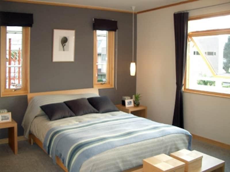 奥の壁だけダークグレーの落ち着いた布クロスで張り分け。カーペット敷きの床と断熱防音性能の高い窓でとても静かな寝室に(スウェーデンハウス)