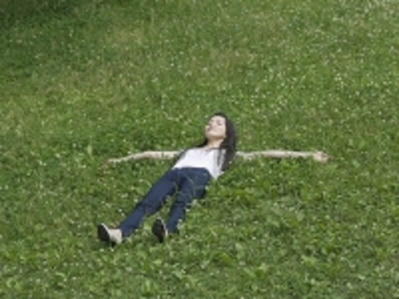 緑に寝転ぶ女性