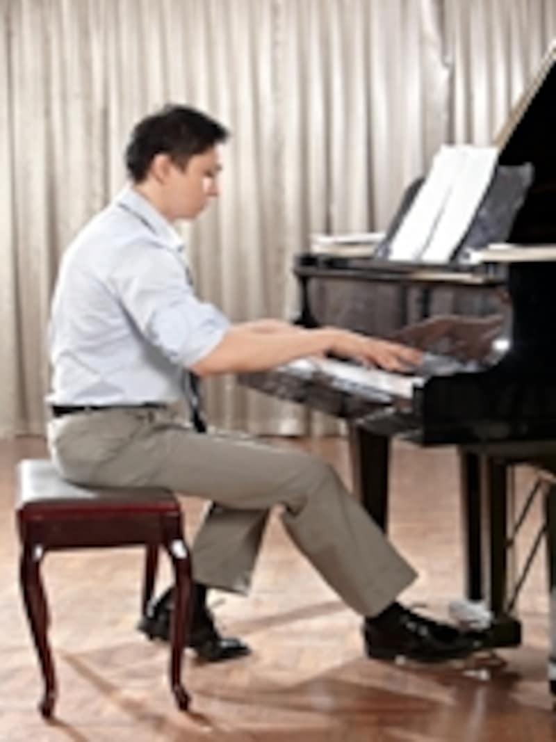 男性がピアノを弾いている写真