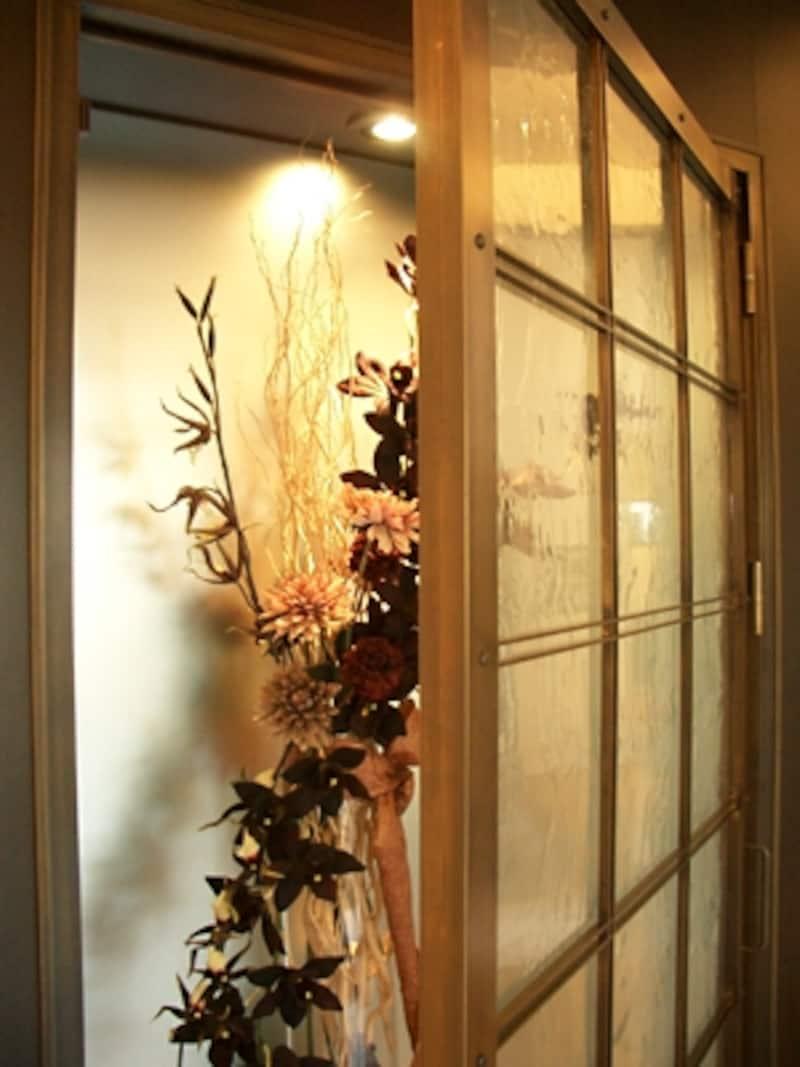 玄関ドアを開けて真正面にある大型ニッチを開けたところ。扉は真鍮の枠にアンティークガラスをはめ込んである。