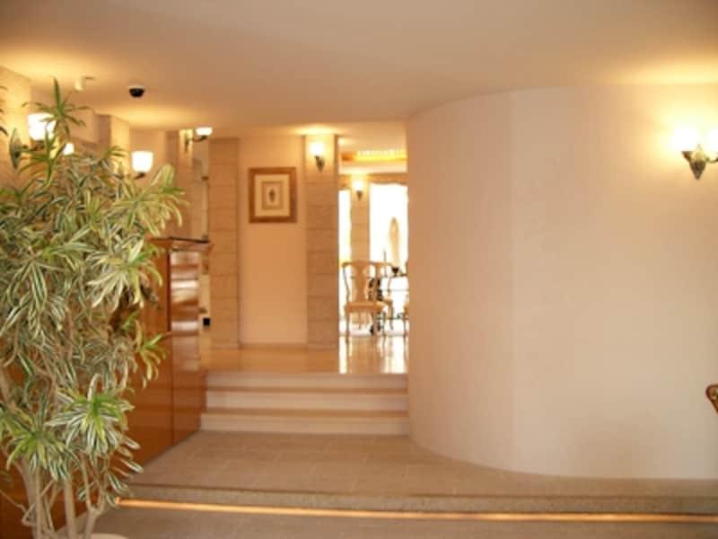 接客コーナーを右手に見ながら、訪れる人を家の中に優しく招き入れる曲線を描く壁(ハウゼ)