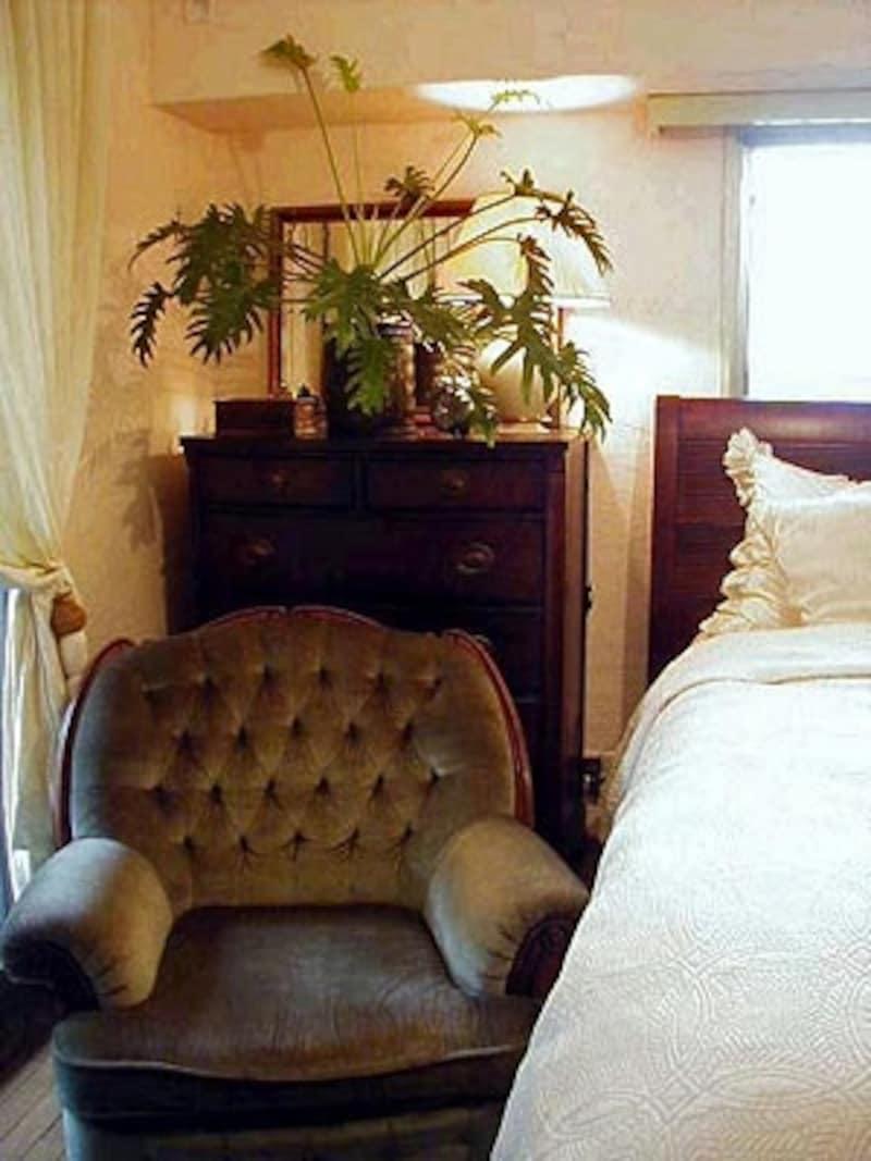 最初に漆喰塗りをした寝室。ゆったりとした大きな一人がけのソファはカリモク製。後ろに見えるチェストは50年前のアメリカ製のものをリペアしたもの。