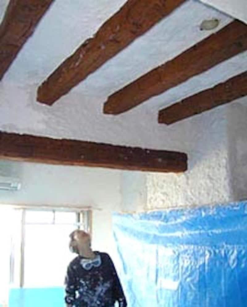 仕上がった天井を見上げるKさん。ブルーのシートで本棚や暖炉を養生してある。