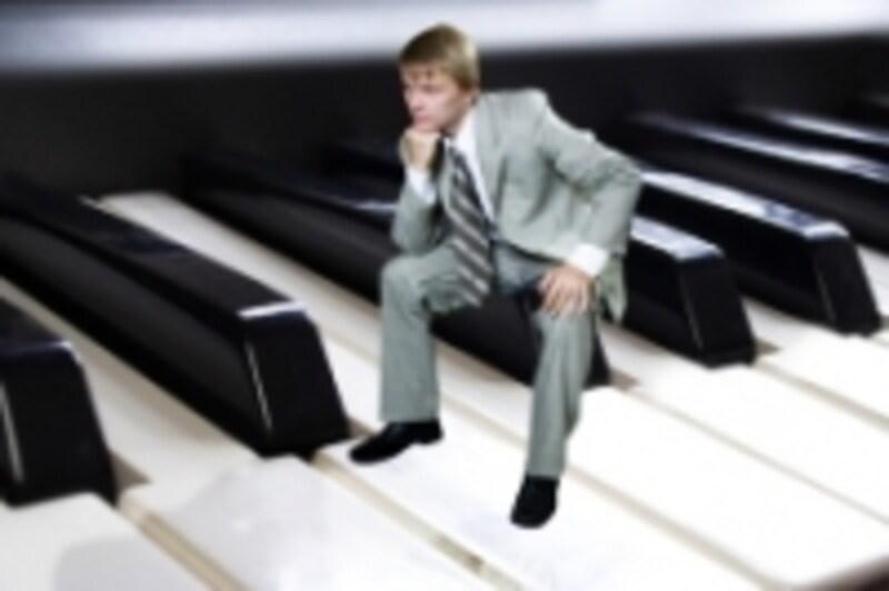 鍵盤の上で考える男性