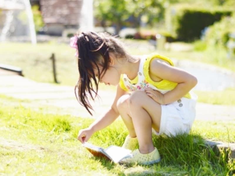 外で本を開く女の子の画像
