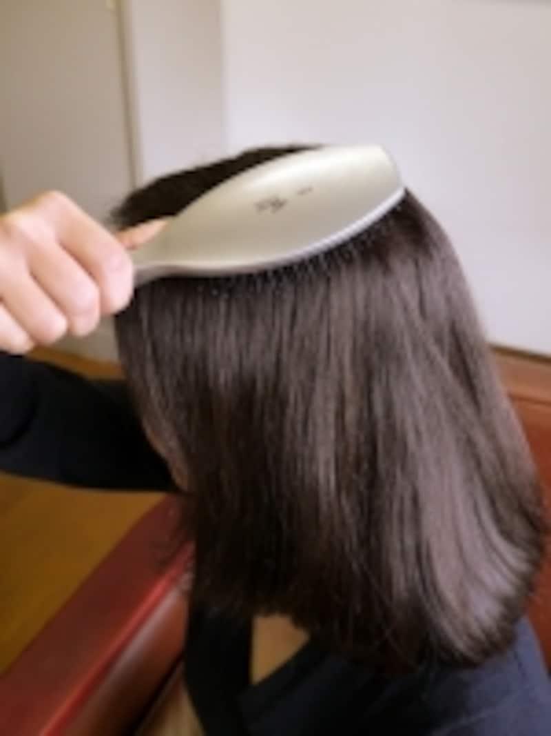 頭皮にブラシの先をあて、上から下に髪をとかします