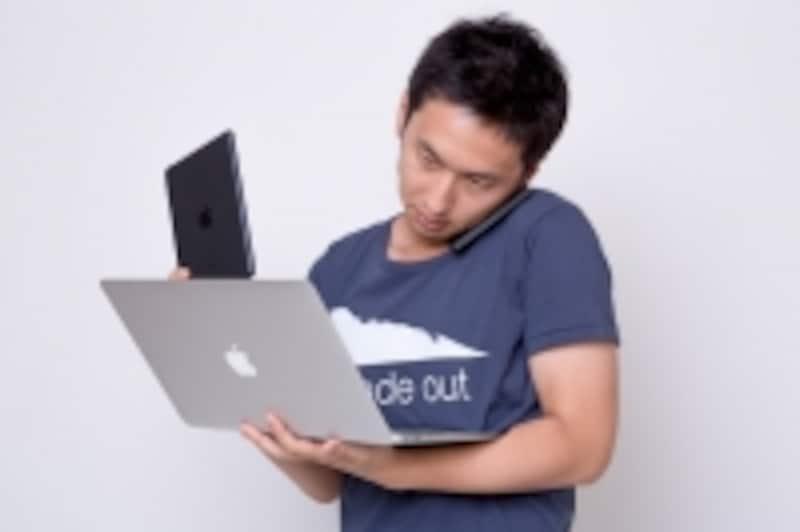 iphoneとPCを使う男性