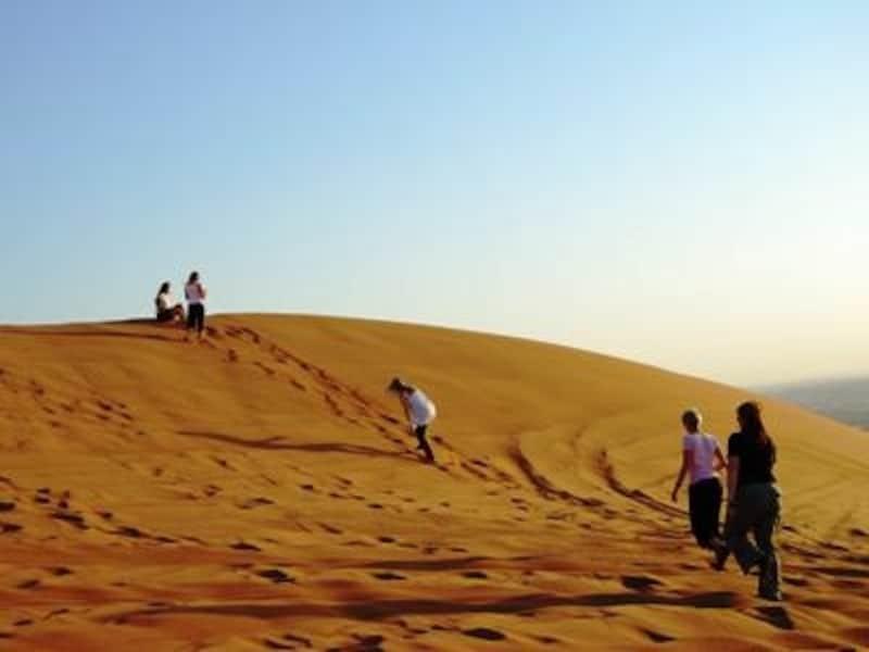 広大な砂漠をバックグラウンドにはしゃぐ学生達