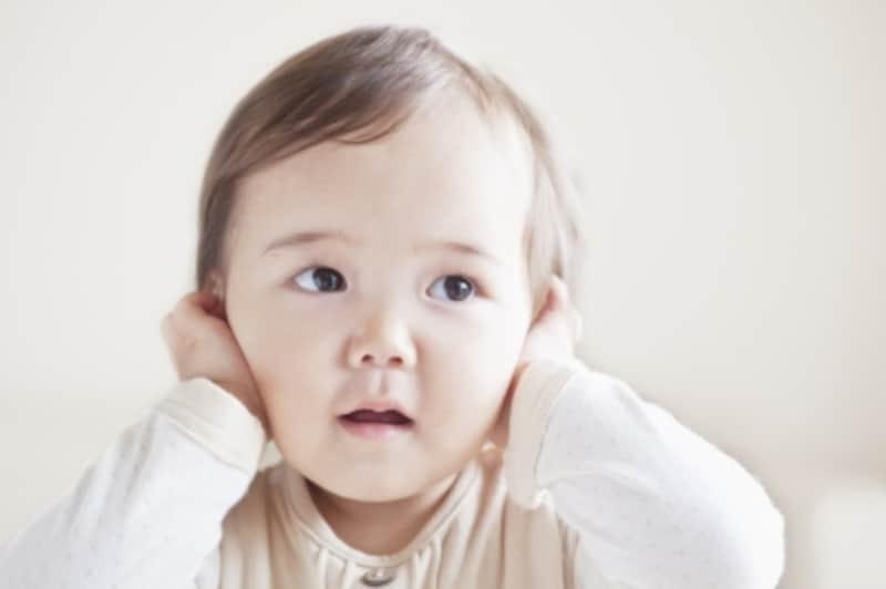 耳を塞いでいる乳幼児