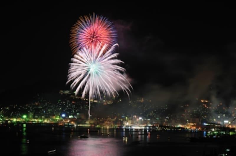 長崎の夜景を背景に花火が咲き誇ります