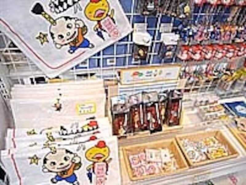 マスコットキャラクターの関連グッズ、缶バッジ200円、ピンバッジ400円、ウォッシュタオル525円など