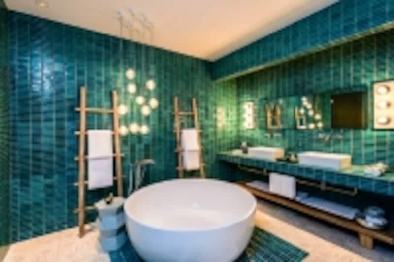 丸いバスタブとグリーンのタイルが個性的なバスルーム