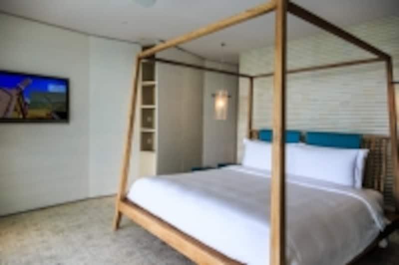 大きめキングサイズのオリジナルベッドを配したシンプルな寝室