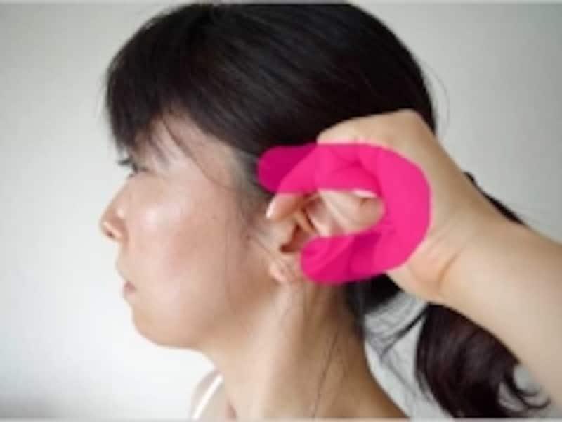 耳に指をかけて側頭部を押す