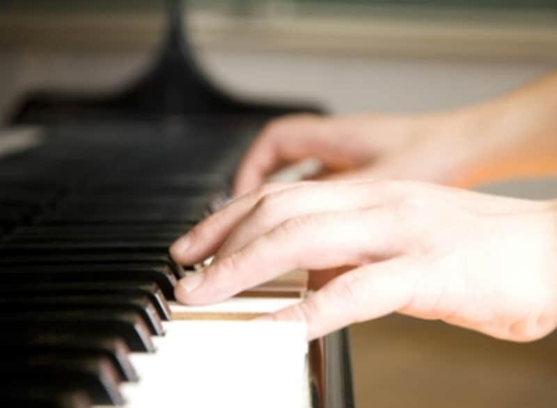 手とピアノ鍵盤の写真