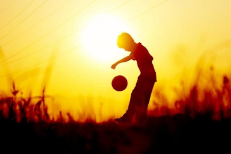 夕暮れ時のサッカー少年