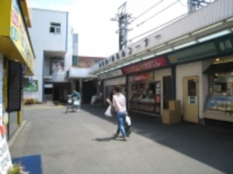 西武新宿線鷺ノ宮駅の、商店街のある南口駅前。店舗の先に駅への入り口があり、その奥は駐輪場