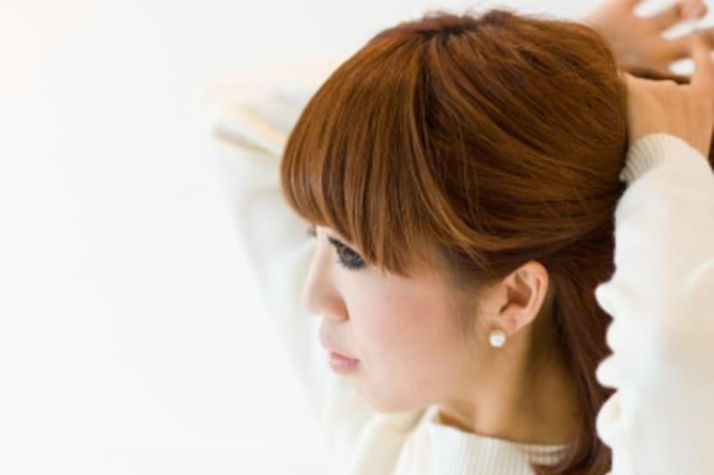 女性が髪の毛を触っている写真