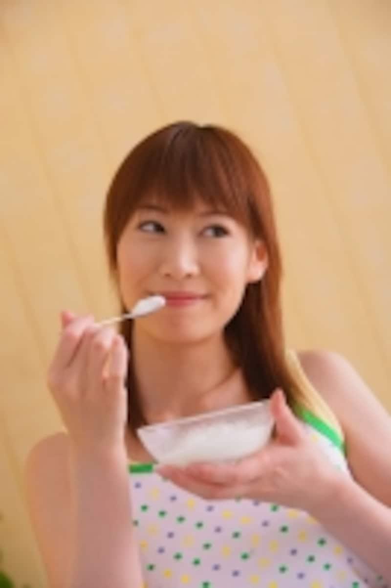 ヨーグルトを食べている女性